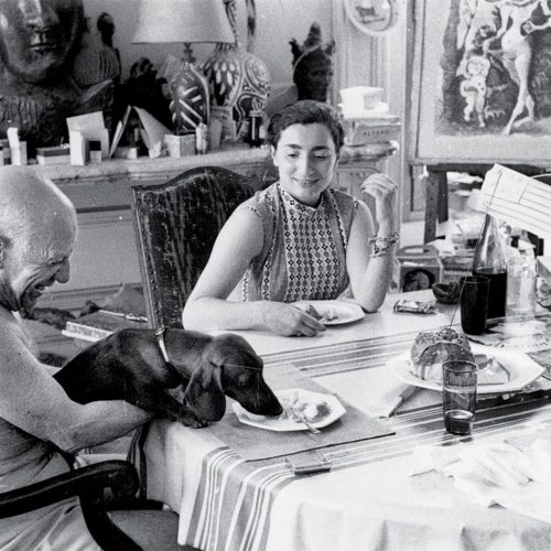 Picasso and Jacqueline sharing lunch at home with Lump - the dachshund, 1957