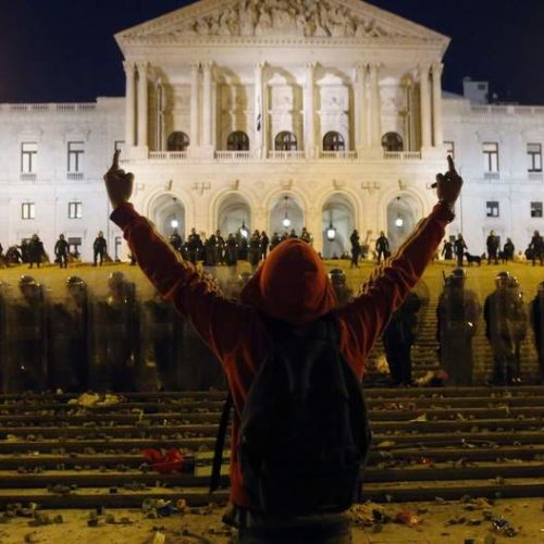 A protester makes obscene gestures to riot police officers outside Parliament during clashes at 24-hour nationwide general strike in Lisbon, November 14, 2012. Spanish and Portuguese workers will stage the first coordinated general strike across the Iberian Peninsula on Wednesday, shutting transport, grounding flights and closing schools to protest against spending cuts and tax hikes. REUTERS/Rafael Marchante (PORTUGAL - Tags: CIVIL UNREST BUSINESS EMPLOYMENT POLITICS)
